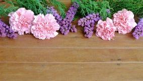 Flores rosadas y púrpuras dulces en la tabla de madera Foto de archivo libre de regalías