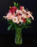 Flores rosadas y rojas hermosas en un florero Foto de archivo