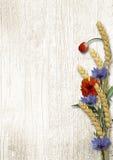 Flores salvajes con las espiguillas en un fondo de madera blanco Imagenes de archivo