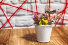 Flores secadas em uma cubeta branca, cubeta com a flor secada no fundo de madeira fotografia de stock