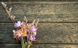 Flores secadas en piso de madera Imagenes de archivo