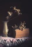 Flores secadas no vaso do metal com livro antigo Imagem de Stock Royalty Free