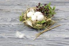 Flores selvagens, velas da igreja e ninho com ovos Fotografia de Stock