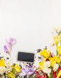 Flores vazias do sinal e da mola de arden: narcisos amarelos e açafrões no fundo de madeira branco, vista superior Foto de Stock Royalty Free