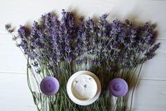 Flores, velas e creme da alfazema em um fundo de madeira branco imagem de stock royalty free