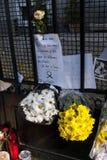 Flores, velas y muestras contra attentado terrorista en París, colocada delante de embajada francesa en Madrid, España Imagen de archivo libre de regalías
