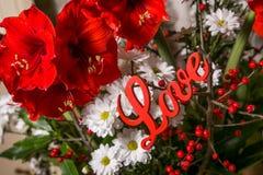 Flores vermelhas com amor de madeira do sinal Fotografia de Stock