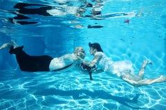 Flores vermelhas de mergulho de beijo do casamento subaquático dos noivos Fotos de Stock