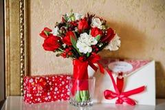 Flores vermelhas do ramalhete da noiva com envelope Fotos de Stock