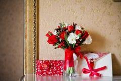 Flores vermelhas do ramalhete da noiva com envelope Imagem de Stock Royalty Free