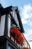 Flores vermelhas na caixa de janela na constru??o de Tudor foto de stock royalty free