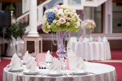 Flores, vidros de vinho, guardanapo e salada na tabela para o banquete Imagem de Stock Royalty Free
