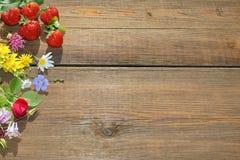 Flores y bayas del verano en tablero de madera del Grunge Imágenes de archivo libres de regalías