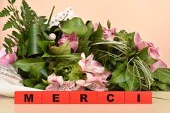 Flores y bloques de madera rojos con el mensaje de Merci imagen de archivo