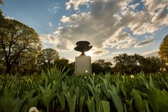 Flores y esculturas en el parque de la ciudad en la puesta del sol foto de archivo