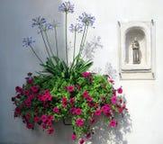 Flores y figurilla religiosa Foto de archivo libre de regalías