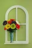 Flores y florero por una ventana Fotografía de archivo
