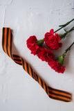 Flores y George Ribbon del clavel en fondo ligero abstracto Día de la victoria - 9 de mayo Jubileo 70 años Fotos de archivo