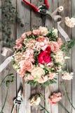 Flores y herramientas de jardín La tabla de trabajo del florista con el fondo de madera gris de los accesorios Imagen de archivo libre de regalías