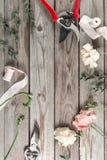 Flores y herramientas de jardín La tabla de trabajo del florista con el fondo de madera gris de los accesorios Fotografía de archivo libre de regalías