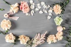 Flores y herramientas de jardín La tabla de trabajo del florista con el fondo de madera gris de los accesorios Copie el espacio Fotos de archivo
