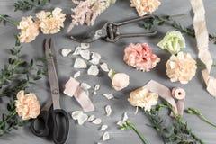 Flores y herramientas de jardín La tabla de trabajo del florista con el fondo del gris de los accesorios Foto de archivo libre de regalías