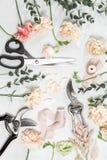 Flores y herramientas de jardín La tabla de trabajo del florista con los accesorios enciende el fondo de madera Foto de archivo libre de regalías