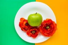 Flores y manzana en fondo colorido Fotografía de archivo libre de regalías