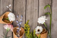Flores y pétalos hermosos en conos de la oblea en fondo de madera Foto de archivo libre de regalías