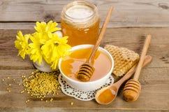 Flores y productos amarillos miel, polen, panales de la abeja Foto de archivo