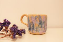 Flores y taza violetas con muchos colores imagen de archivo