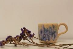 Flores y taza violetas con muchos colores foto de archivo