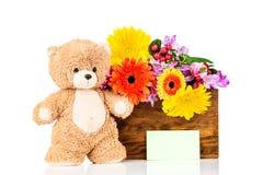 Flores y un oso de peluche Imágenes de archivo libres de regalías