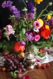 Flores y uvas en una tabla de madera - escena elaborada de la cosecha de la acción de gracias Imagenes de archivo