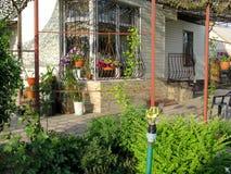 Flores y vegetación alrededor de la casa Imagen de archivo libre de regalías
