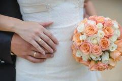 Floresce as mãos das alianças de casamento Foto de Stock