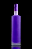 Florescent purple alcohol bottle. On dark background Stock Photos