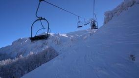 Floresta e esquiadores da neve em um elevador de esqui pov filme