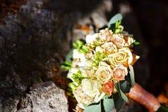 Florezca el ramo de la boda de flores blancas y rosadas con los anillos de bodas del oro de novias, en las rocas Imágenes de archivo libres de regalías