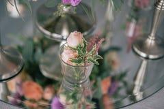 Florezca el ramo en vade con las velas en la tabla adornada blanca Foto de archivo libre de regalías