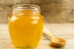 Florezca el tarro de la miel con la cuchara en fondo de madera Imagen de archivo libre de regalías