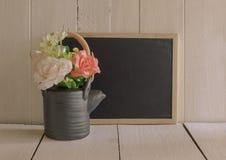 Florezca en un pote del té negro con el tablero de dibujo negro Fotografía de archivo