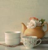 Florezca en un pote del té y una taza amarillos del vintage de café en b de madera Imágenes de archivo libres de regalías