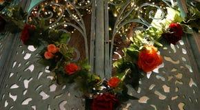 Florezca la guirnalda en las puertas que miran a escondidas en jardín iluminado por el sol fotografía de archivo