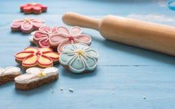 Florezca las galletas y el rodillo formados del pan de jengibre en una tabla de madera azul fotos de archivo