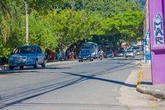 FLORIANOPOLIS BRASILIEN - MAJ 08, 2016: körning för några bilar på gatan, gångare som väntar på bussen och några stora träd på se Arkivbilder