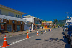 FLORIANOPOLIS, BRAZIL - MAY 08, 2016: nice little houses with stores in the lower level, cars parked in one side of the. Street, some cones placed in the middle Royalty Free Stock Image