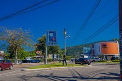 FLORIANOPOLIS, BRAZIL - MAY 08, 2016: pedestrian crossing the street while some cars drive trough the street.  Stock Photography