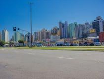 FLORIANOPOLIS, EL BRASIL - 8 DE MAYO DE 2016: la porción de coches parqueó en un aveneu vacío con el horizonte de los edificios c Fotografía de archivo libre de regalías
