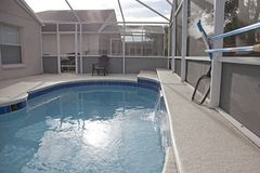 Florida backyard swimming pool. A sunny day by a swimming pool at a screened in yard stock photos